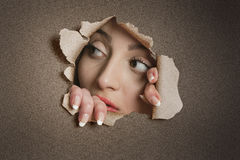 Young Middle eastern woman looking away from ripped paper hole Royalty Free Stock Photos