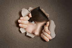 Young Middle eastern woman peeking from ripped white paper hole Royalty Free Stock Photos
