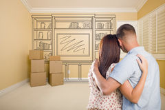 Young Military Couple In Empty Room with Shelf Drawing on Wall Royalty Free Stock Photos