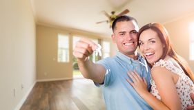 Young Military Couple with House Keys In Empty Room of New Home royalty free stock photo