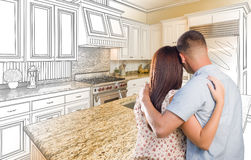 Young Military Couple Inside Custom Kitchen and Design Drawing C. Young Military Couple Looking Inside Custom Kitchen and Design Drawing Combination Royalty Free Stock Images