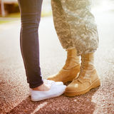 Young military couple kissing each other, homecoming concept. Warm orange toning applied Royalty Free Stock Image