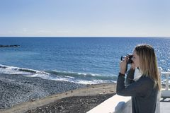 Young millennial female of Caucasian ethnicity holding a camera and taking a photograph facing towards the ocean. Horizontal shot of young, blonde woman, taking Stock Images
