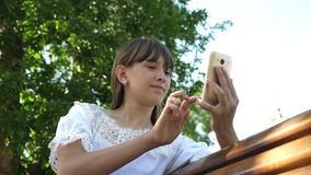 Young millennial woman in the Arboretum, making gestures on the phone display. A young girl using a smartphone is. Writing letter on a bench in a beautiful royalty free stock image