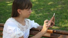 Young millennial woman in the Arboretum, making gestures on the phone display. A young girl using a smartphone is. Writing letter on a bench in a beautiful stock image