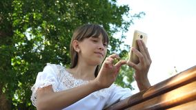 Young millennial woman in the Arboretum, making gestures on the phone display. A young girl using a smartphone is. Writing letter on a bench in a beautiful royalty free stock photos