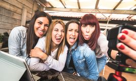 Young millennial women taking selfie for streaming platform through digital action web cam - Influencer marketing concept. With millenial girls having fun stock photo