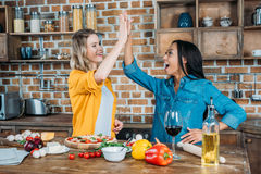 Young miltiehnic women giving high five while cooking in kitchen Royalty Free Stock Images