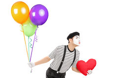 Young mime artist with balloons and red heart giving kisses Royalty Free Stock Photography