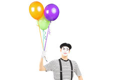 Young mime artist holding balloons and looking at camera Royalty Free Stock Image