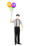 Young mime artist holding balloons and looking at camera Stock Image