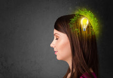 Young mind thinking of green eco energy with lightbulb. On grungy background Stock Image