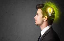 Young mind thinking of green eco energy with lightbulb. On grungy background Royalty Free Stock Image