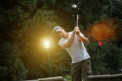 Young minigolf player hits a red ball on a minigolf field. A lan Royalty Free Stock Image