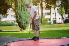 Young minigolf player tries to put a black ball into the hole Stock Photography
