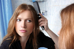 Young of a mirror correcting hairs Stock Images
