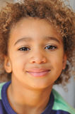 Young mixed race boy with curly hair. Curly hair mixed race boy posing for portrait stock photography