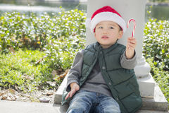 Young Mixed Race Boy Holding Candy Cane Wearing Santa Hat. Cute Mixed Race Boy Sitting Wearing Christmas Santa Hat and Enjoying A Candy Cane Royalty Free Stock Photos