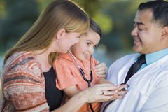 Young Mixed Race Boy, Mother and Doctor Experimenting With Stethoscope Stock Photos