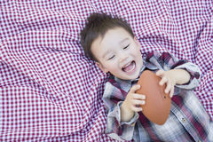 Young Mixed Race Boy Playing with Football on Picnic Blanket Stock Image