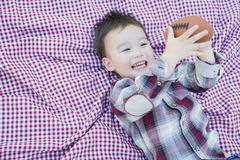 Young Mixed Race Boy Playing with Football on Picnic Blanket Stock Images