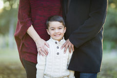 Young Mixed Race Boy Portrait Outdoors With Parents Behind Stock Photo