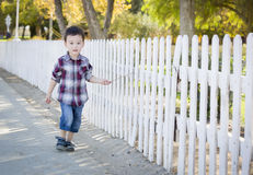 Young Mixed Race Boy Walking with Stick Along White Fence Royalty Free Stock Photos