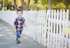 Young Mixed Race Boy Walking with Stick Along White Fence Stock Images