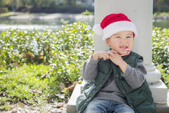 Young Mixed Race Boy Wears Santa Hat Eats Candy Cane Stock Image
