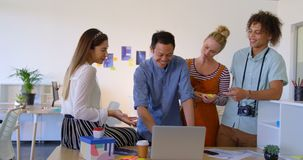 Young mixed-race business people working on laptop at desk in modern office and laughing together 4k. Front view of young mixed-race business people working on stock footage