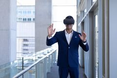 Young mixed-race businessman using virtual reality headset in modern office. Front view of happy young mixed-race businessman using virtual reality headset royalty free stock photography