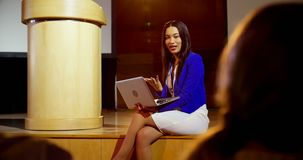 Young mixed-race businesswoman with laptop speaking in seminar at auditorium 4k. Front view of beautiful young mixed-race businesswoman with laptop speaking in stock video