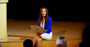 Young mixed-race businesswoman with laptop speaking in seminar at auditorium 4k. Front view of pretty young mixed-rcae businesswoman with laptop speaking in stock video footage