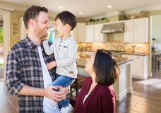 Young Mixed Race Caucasian Chinese Family In Custom Kitchen. Young Mixed Race Caucasian and Chinese Family Inside Custom Kitchen royalty free stock image