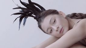 Young mixed race caucasian woman vogue portrait with feather mohawk accessory wearing black bodysuit. stock video footage