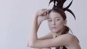 Young mixed race caucasian woman vogue portrait with feather mohawk accessory wearing black bodysuit. Young mixed race caucasian woman vogue portrait with stock video footage