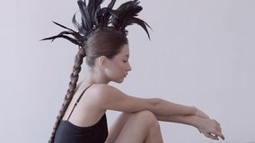 Young mixed race caucasian woman vogue portrait with feather mohawk accessory wearing black bodysuit. Young mixed race caucasian woman vogue portrait with stock video