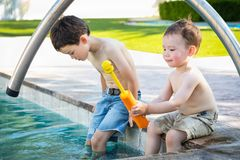 Young Mixed Race Chinese Caucasian Brothers Playing At The Pool. Young Mixed Race Chinese and Caucasian Brothers Playing At The Pool stock photography