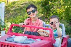 Young Mixed Race Chinese Caucasian Brothers Wearing Sunglass. Young Mixed Race Chinese and Caucasian Brothers Wearing Sunglasses Playing In Toy Car stock image