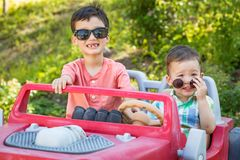 Young Mixed Race Chinese and Caucasian Brothers Wearing Sunglasses Playing In Toy Car. Young Mixed Race Chinese and Caucasian Brothers Wearing Sunglasses Playing royalty free stock photography