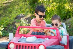 Young Mixed Race Chinese and Caucasian Brothers Wearing Sunglasses Playing In Toy Car. Young Mixed Race Chinese and Caucasian Brothers Wearing Sunglasses Playing royalty free stock images