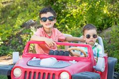 Young Mixed Race Chinese and Caucasian Brothers Wearing Sunglasses Playing In Toy Car. Young Mixed Race Chinese and Caucasian Brothers Wearing Sunglasses Playing stock image