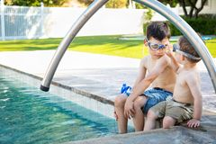 Young Mixed Race Chinese Caucasian Brothers Wearing Swimming Goggles. Young Mixed Race Chinese and Caucasian Brothers Wearing Swimming Goggles Playing At The stock photo
