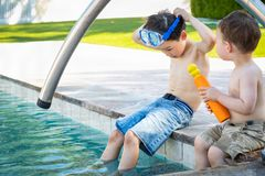 Young Mixed Race Chinese Caucasian Brothers Wearing Swimming Goggles. Young Mixed Race Chinese and Caucasian Brothers Wearing Swimming Goggles Playing At The royalty free stock image
