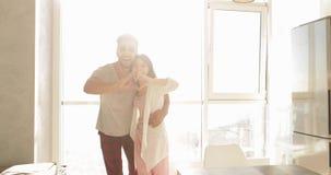Young Mixed Race Couple Apartment Big Window Morning Sunlight, Cute Happy Hispanic Man And Asian Woman Embracing