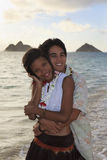Young mixed race couple at the beach. In hawaii at sunrise stock photography