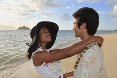 Young mixed race couple at the beach. In hawaii at sunrise royalty free stock photos