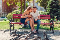 Young mixed race couple in love feeding bidrs in summer park. Man and woman thowing bread to doves stock photography