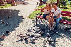 Young mixed race couple in love feeding bidrs in summer park. Man and woman thowing bread to doves. Young mixed race couple in love feeding bidrs in summer park stock photos