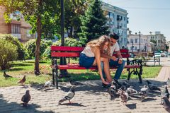 Young mixed race couple in love feeding bidrs in summer park. Man and woman thowing bread to doves. Young mixed race couple in love feeding bidrs in summer park royalty free stock photo